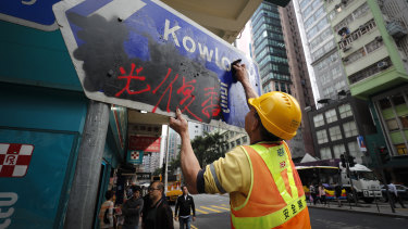 A worker cleans a road sign vandalised by protesters in Causeway Bay, Hong Kong.