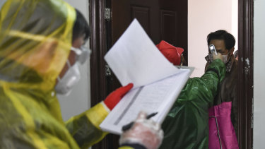 Workers go door to door to check the temperature of residents during a health screening campaign in the Qingshan District of Wuhan.