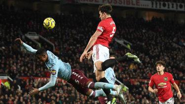 Ezri Konsa Ngoyo of Aston Villa is beaten by Harry Maguire of Manchester United.