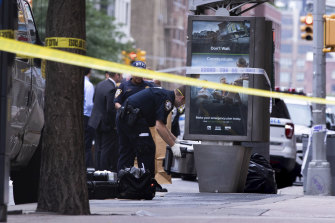 An investigator picks up a suspicious package that was thought to be an explosive device in Manhattan's Chelsea neighbourhood on Friday.