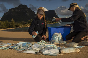 Marine rangers Caitlin Woods and Sallyann Gudge count face masks that have washed up on a Lord Howe Island beach.