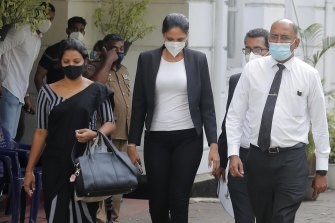 The reigning Mrs World Caroline Jurie, centre, leaves a police station in Colombo after being granted bail.