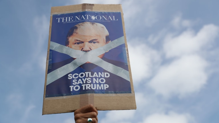 A protester holds up a banner as people gather to protest the visit by US President Donald Trump and first lady Melania Trump, in Turnberry, Scotland, on Saturday July 14.