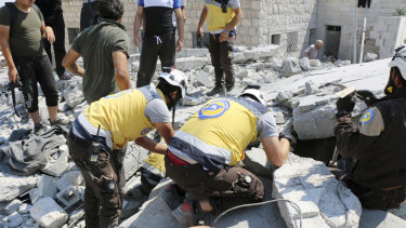 Syrian White Helmet workers search for victims in the rubble of a building hit by airstrikes in Deir al-Sharqi village, Idlib province, Syria, on Saturday.