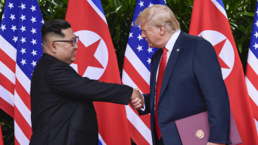"""""""In love"""": North Korea leader Kim Jong-un and US President Donald Trump shake hands at the conclusion of their meetings in Singapore in June."""