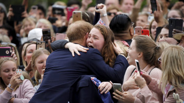 Prince Harry hugs fan India Brown as he arrives at Government Drive.