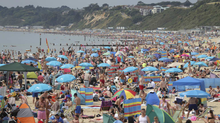 People relax on Bournemouth beach in Dorset , England, on Sunday as the hot weather continued across the country.