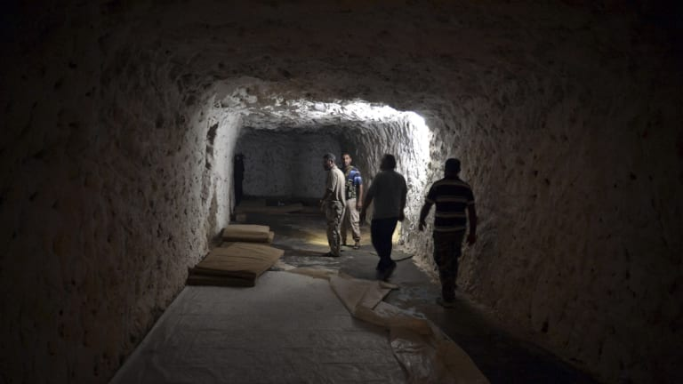 Fighters with the Free Syrian army walk in a cave where they live in order to be protected from bombing in the outskirts of the northern town of Jisr al-Shughur, Syria, west of the city of Idlib.