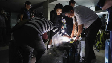 People use torches to check passengers' luggage at a terminal of Asahikawa airport.