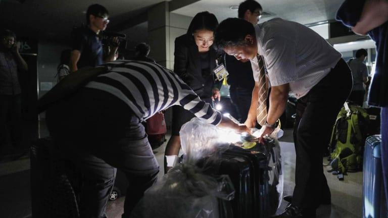 People use torches to check passengers' luggage at a terminal of Asahikawa airport.
