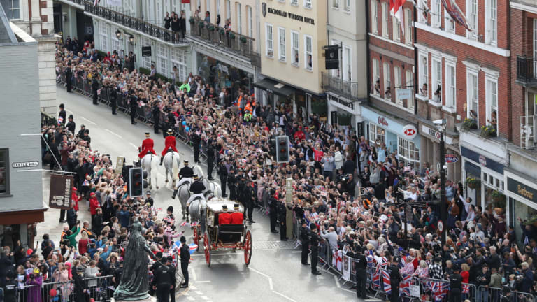 Crowds cheer as the couple leave in a carriage following their wedding ceremony at St George's Chapel.