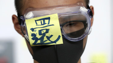 """A protester wears a goggle with a word """"Return"""" during a protest at the arrival hall of the Hong Kong International Airport in Hong Kong."""