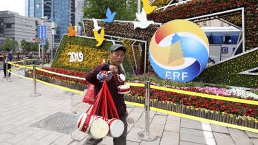 A man selling Chinese drums walks past a decoration promoting the upcoming Belt and Road Forum in Beijing.