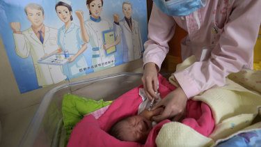 A baby receives a vaccine shot next to a poster that reads 'Standardise vaccination and build a healthy China'.