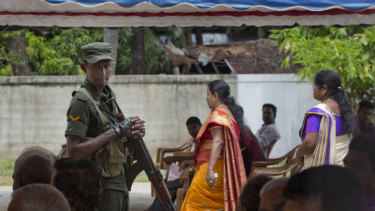 A soldier stands guard amid Catholics attending Mass outside St Joseph's church in Thannamunai, Sri Lanka, on Tuesday.