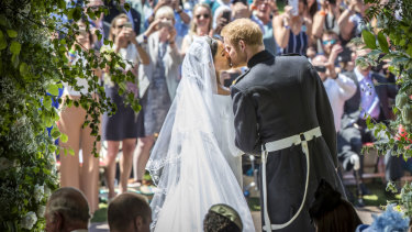 Meghan Markle and Prince Harry kiss on the steps of St George Chapel.