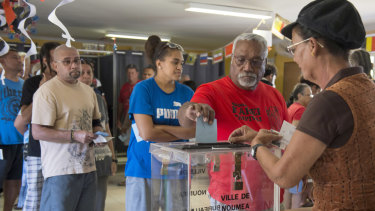A man casts his vote at a polling station in Noumea, New Caledonia.
