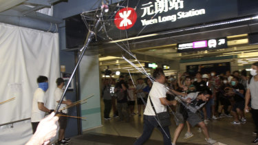 Men armed with metal rods and wooden poles attack commuters on Sunday.
