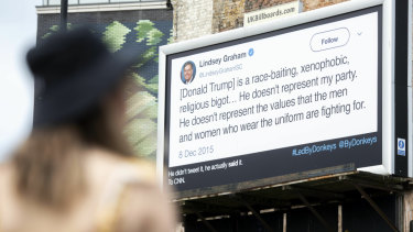 A woman views an anti-Donald Trump billboard displayed in London by the campaign group Led By Donkeys on Sunday.