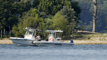 Emergency workers patrol an area near where the duck boat capsized.