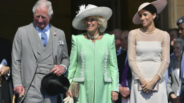 From left, Prince Charles, his wife Camilla, the Duchess of Cornwall, and Meghan, the new Duchess of Sussex attend a garden party at Buckingham Palace in London.