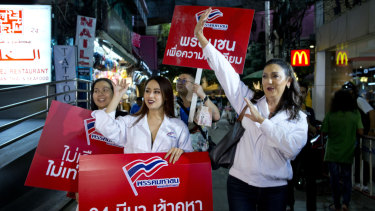 Pauline Ngarmpring, right, a transgender person and a prime ministerial candidate, and Namklenginarin, centre, a candidate for the parliament, greet people in Bangkok.