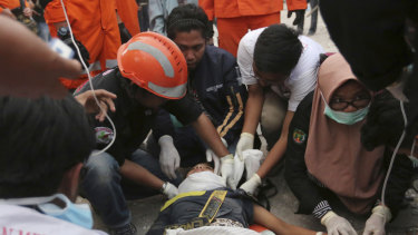 Rescuers check a survivor at a restaurant damaged by massive earthquakes and tsunami in Palu.