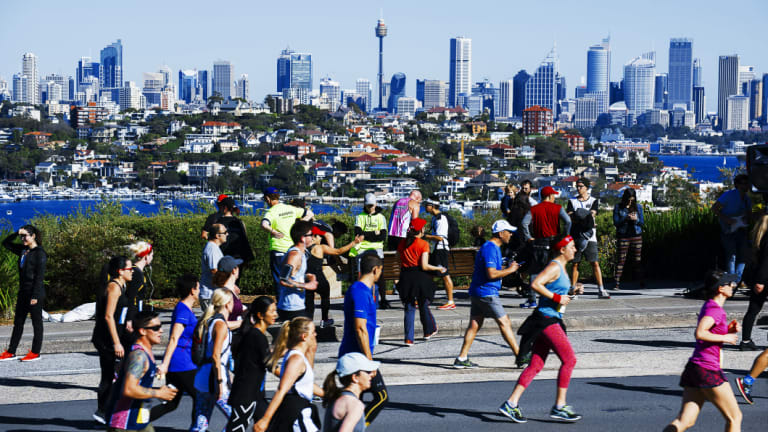Fun-runners battle up Heartbreak Hill as the city shines in the background.