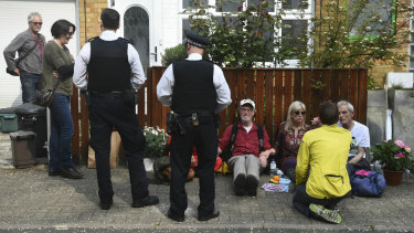 Police officers talk with climate activists  glued together outside UK Labour Party leader Jeremy Corbyn's house in north London on Wednesday.