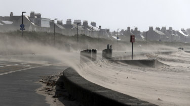 Strong winds whip sand across the seafront road at Troon Beach in Northern Ireland on Wednesday.