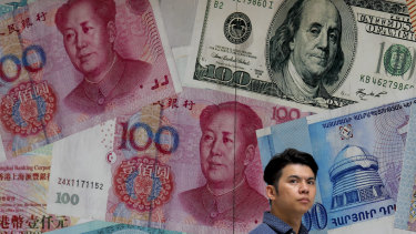 A man walks past a money exchange shop decorated with different banknotes in Hong Kong.