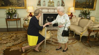 Theresa May kneels before the Queen at Buckingham Palace, where the monarch invited May in 2016 to become Prime Minister and form a new government.