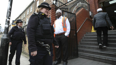 Police officers patrol the area outside Finsbury Park Mosque in London following the Christchurch mosque attacks, as worshipers begin to arrive for the Friday prayer service.