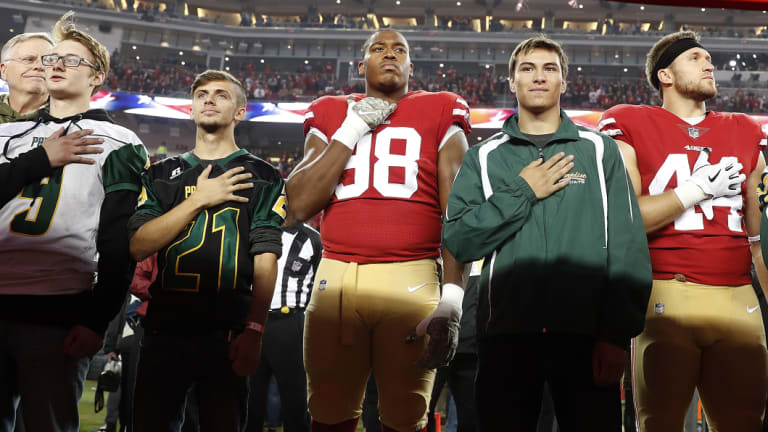 Tribute: San Francisco 49ers defensive end Ronald Blair III (98) and fullback Kyle Juszczyk (44) stand with students from Paradise High School during the national anthem before an NFL football game between the 49ers and the New York Giants in Santa Clara, California, on Monday.