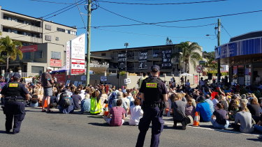 Protesters sit in silence for seven minutes last month to mark seven years of offshore detention for some of the refugees being kept in the  Kangaroo Point hotel.