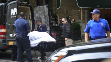 The body of designer Kate Spade is removed from her apartment building in New York on Tuesday.
