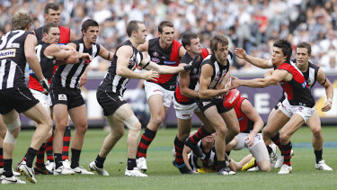 Collingwood defender Alan Toovey finds himself at the front of a queue of Magpies and Bombers.
