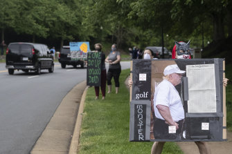 Activists hold signs as the motorcade for President Donald Trump departs Trump National Golf Club on May 24.