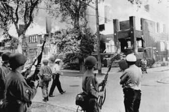 Police and National Guardsmen stand by as fire sweeps through a city block in the wake of race riots in Detroit in 1967.