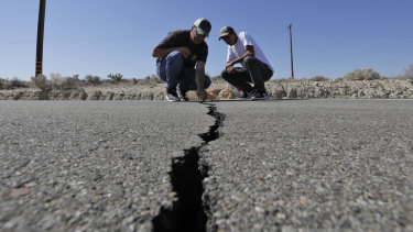 A crack caused by an earthquake on highway 178 outside of Ridgecrest, California is examined by Ron Mikulaco, left, and his nephew, Brad Fernandez.