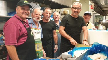 Cypriot Community of Queensland president Stathi Zambas and volunteers slicing half a tonne of calamari to sell at the annual Greek festival, Paniyiri.