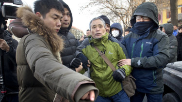 Plainclothes security officers take away one of Wang's supporters.