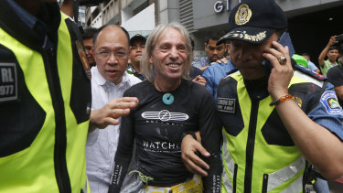Robert being taken away by police after his latest stunt.