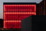 The extruded glass box illuminates at night: flashing red for Anzac Day, hi-vis orange in tribute to SES volunteers during the fires and blue for recently fallen police officers.
