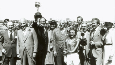 Lloyd Williams holds his first Melbourne Cup, won by Just  A Dash, trained by Tommy Smith, left, and ridden by Peter Cook.