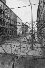 View across the barbed wire entanglements which top the wall into Sebastian Strasse between East and West Berlin.