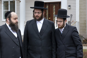 Community members gather outside a rabbi's residence in Monsey, New York, following a stabbing attack during a Hanukkah celebration.