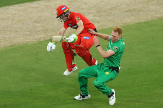 Demolition derby: Sam Harper of the Renegades and Stars bowler Liam Hatcher collide between the wickets.