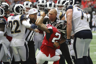 Officials restrain Devonta Freeman during a fight between the Falcons and the Los Angeles Rams.
