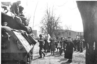 Civilians wave white flags to advancing American troops in March 1945.
